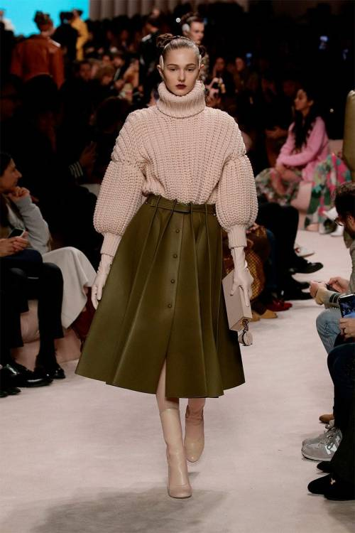 A soft pink sweater tucked into a leather skirt with massive pleats