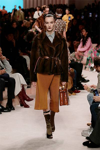A slim-fitted fur jacket and thin leather belts with tiny cases and pendants