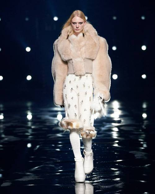 The designer focused on graphic and slightly hypertrophied silhouettes, as well as accessories - fur mittens, hats and scarves, feathers apes and pendants in the form of gold water bottles.